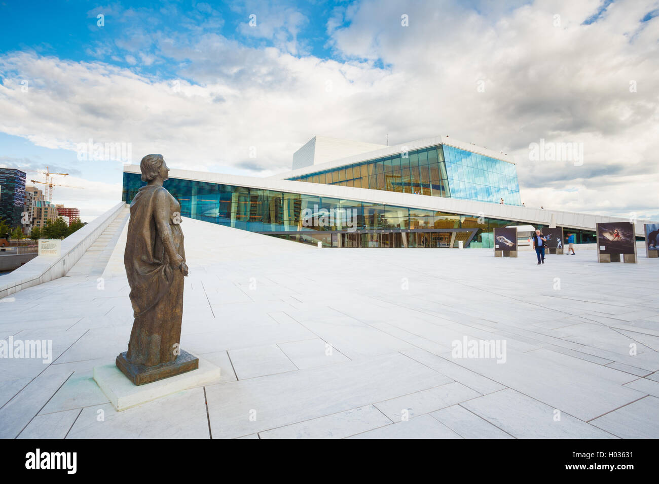 Oslo, Norway - July 31, 2014: Side View Of Glass Facade Of Oslo Opera And Ballet House. The Bronze Statue On White Stock Photo