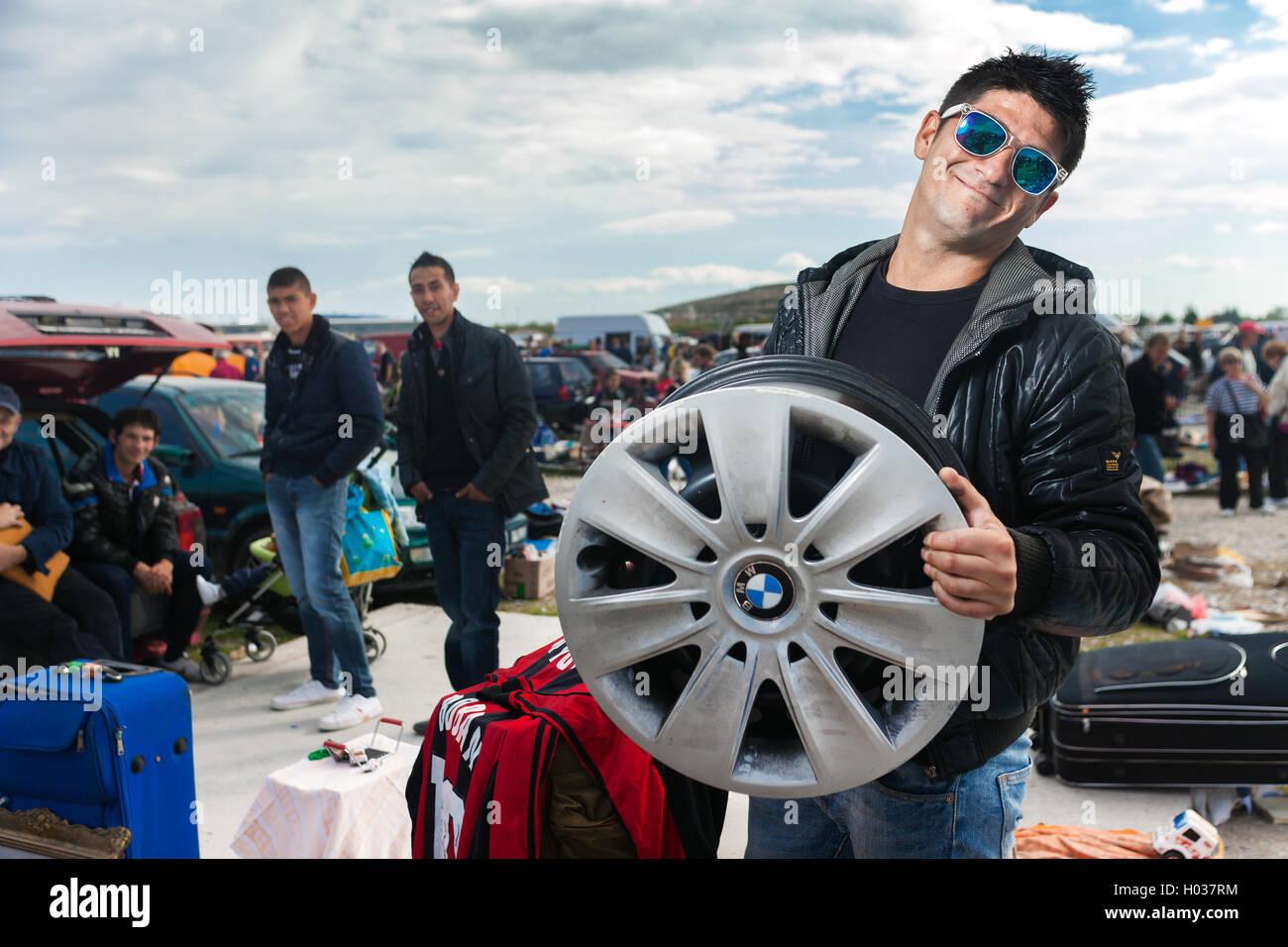 ZAGREB, CROATIA - OCTOBER 20, 2013: Roma salesman holding used car rim at Zagreb's flea market Hrelic. - Stock Image