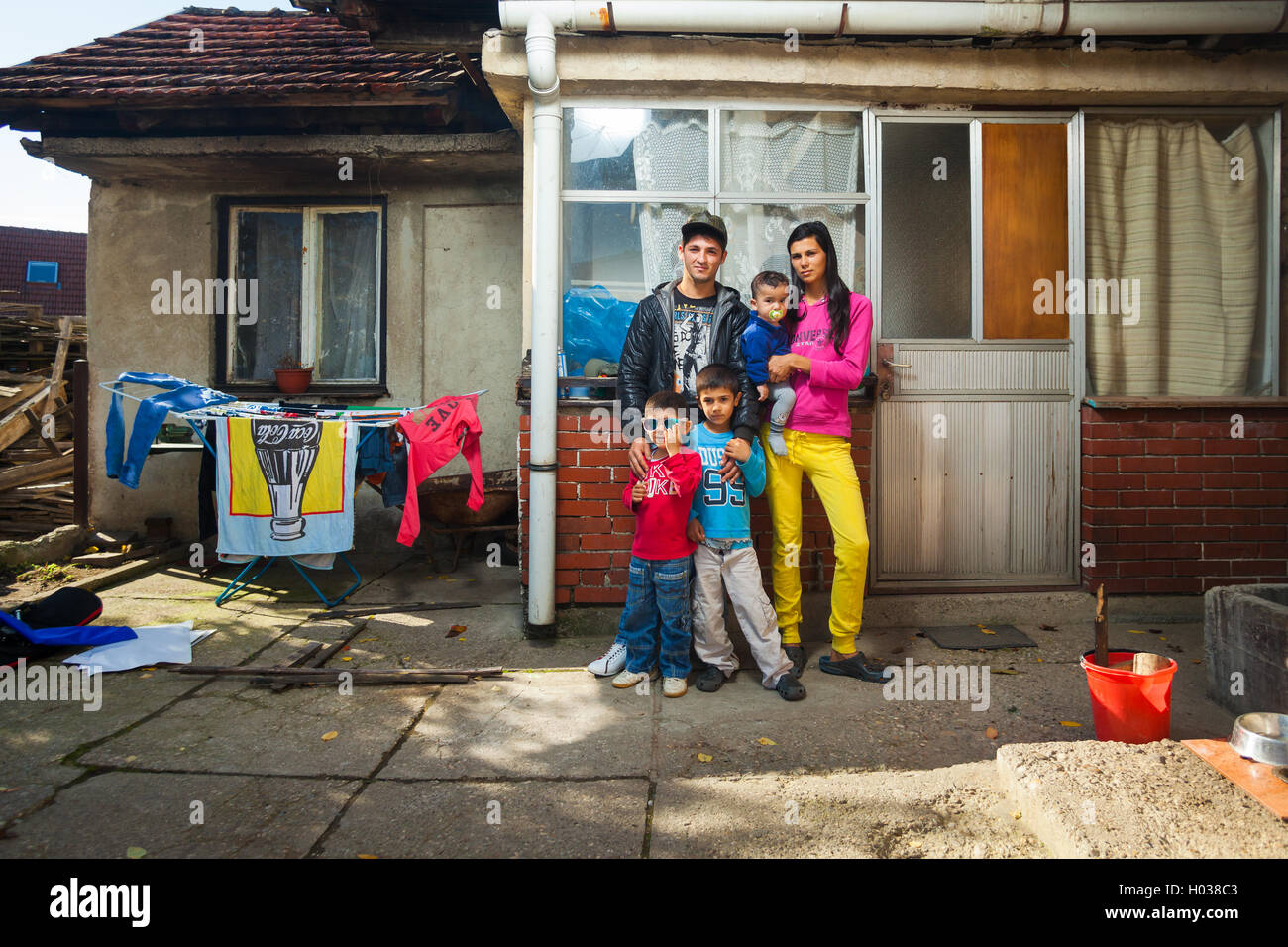 ZAGREB, CROATIA - OCTOBER 21, 2013: Roma family posing in front of their house. - Stock Image
