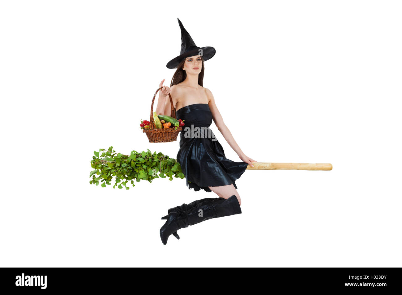 Young woman dressed as a witch carrying vegetable basket and riding a broom. White background. - Stock Image