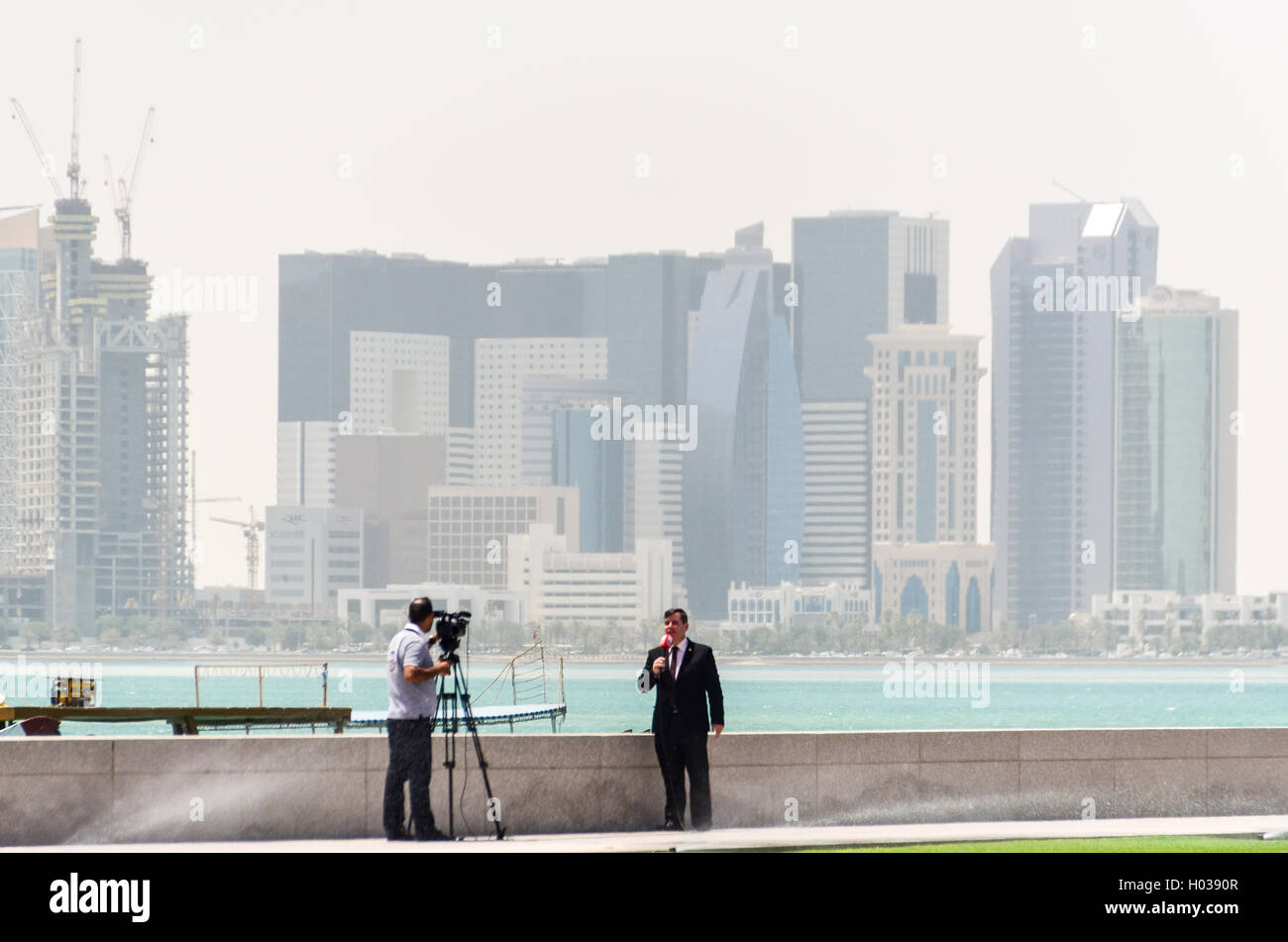 Interview with cameraman and speaker in Doha, with the West Bay financial district in the background - Stock Image