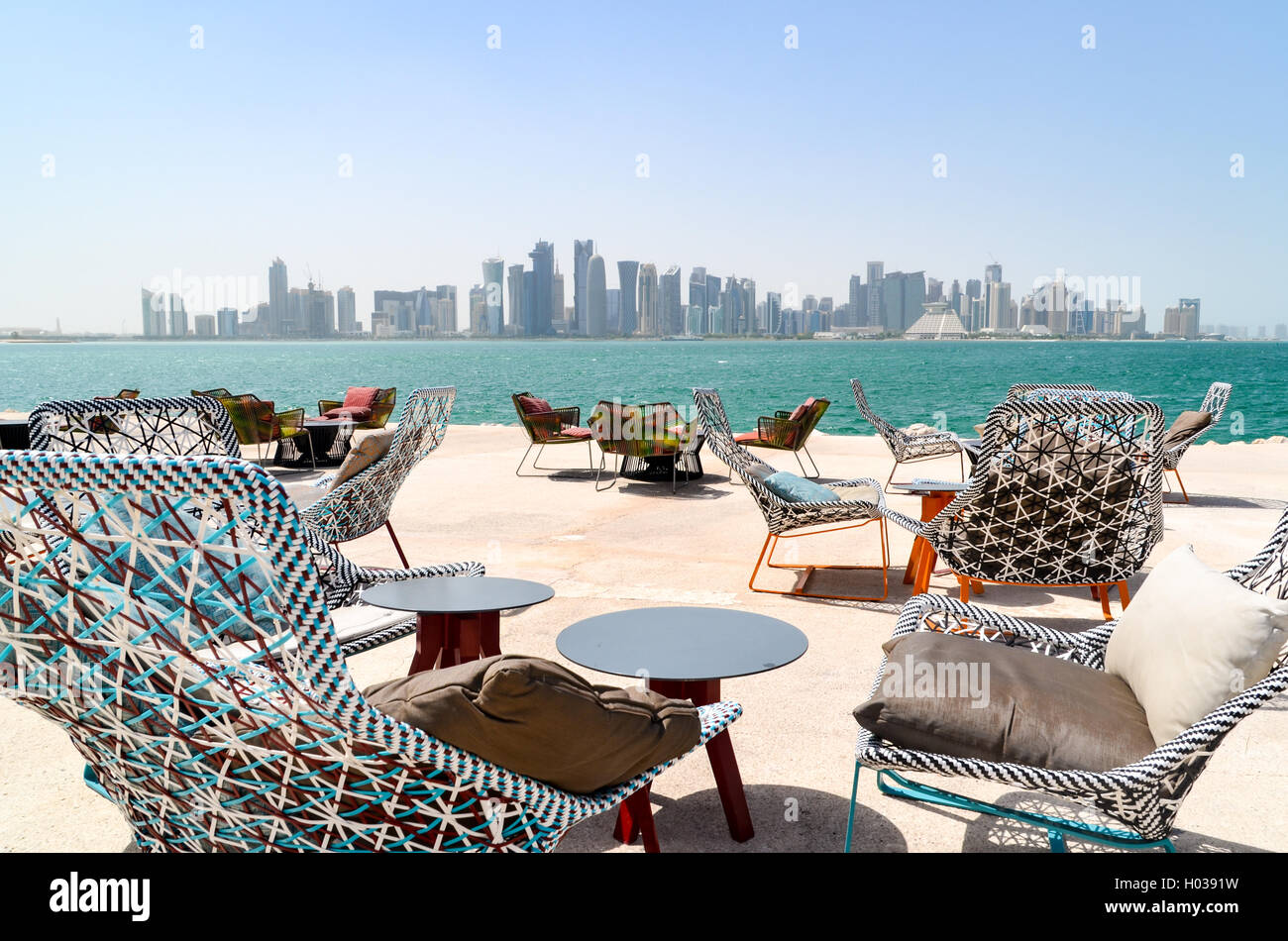 Empty restaurant and snack tables and chairs in Doha, with a view of the West Bay financial district Stock Photo