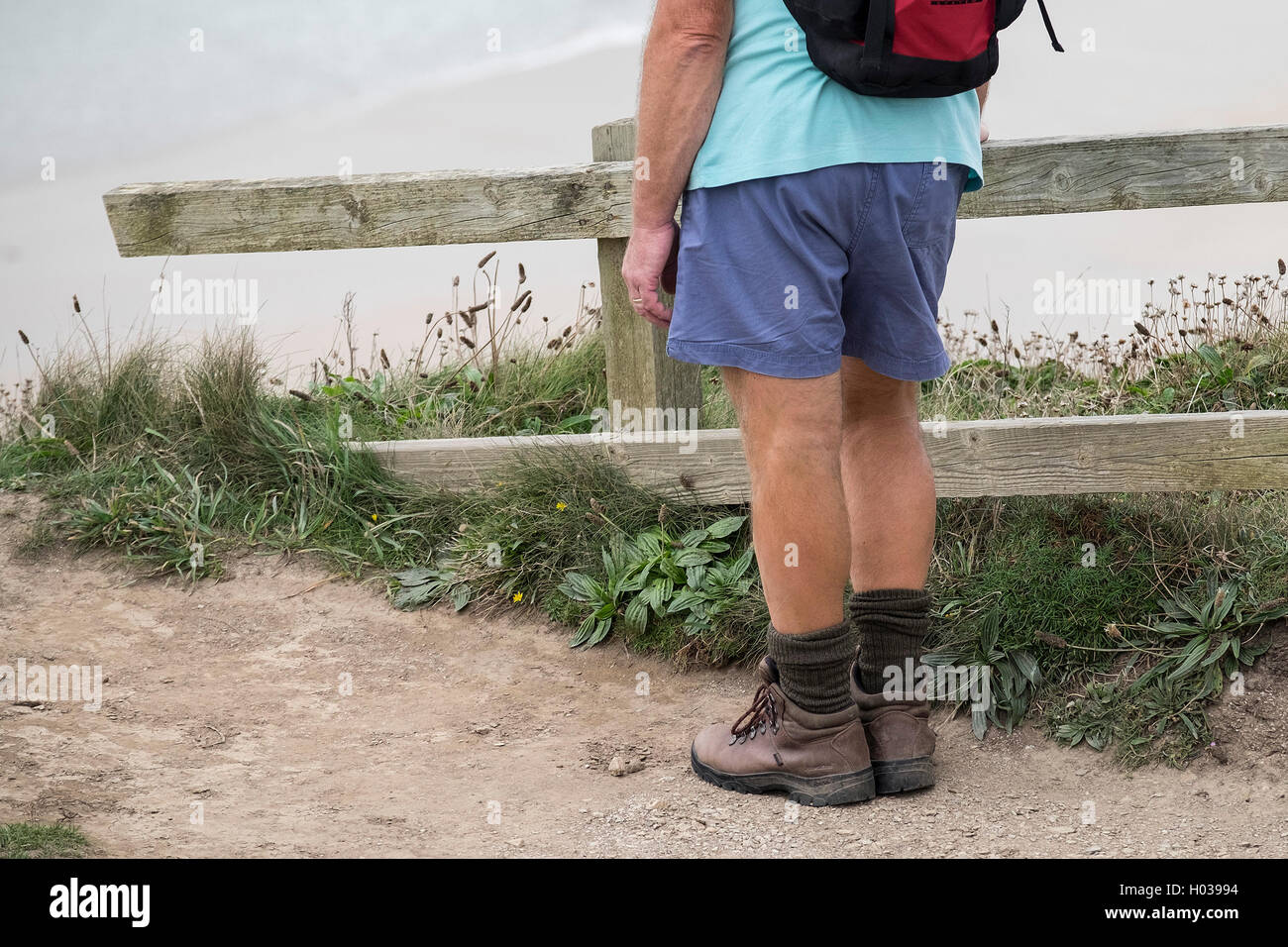 A walker takes a break on the South West Coastal Path in Cornwall. - Stock Image