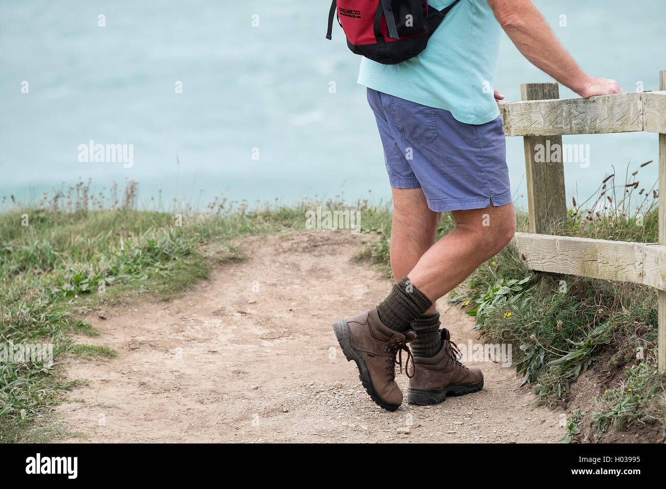 A walker takes a rest on the South West Coastal Path in Cornwall. - Stock Image