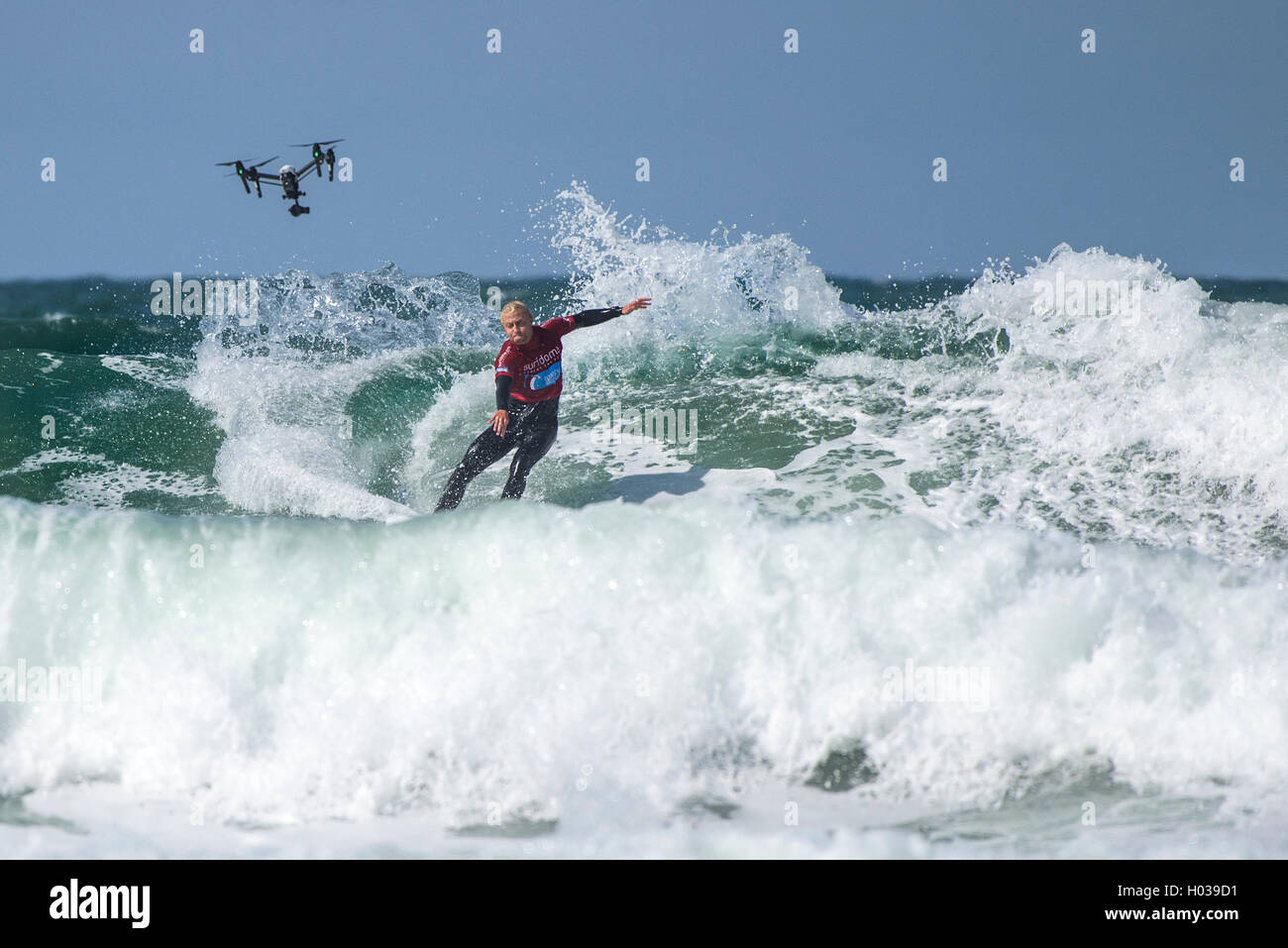 A drone films a competitor in action at the Surfing GB Inter-Clubs Surfing Competition at Fistral in Newquay, Cornwall. - Stock Image