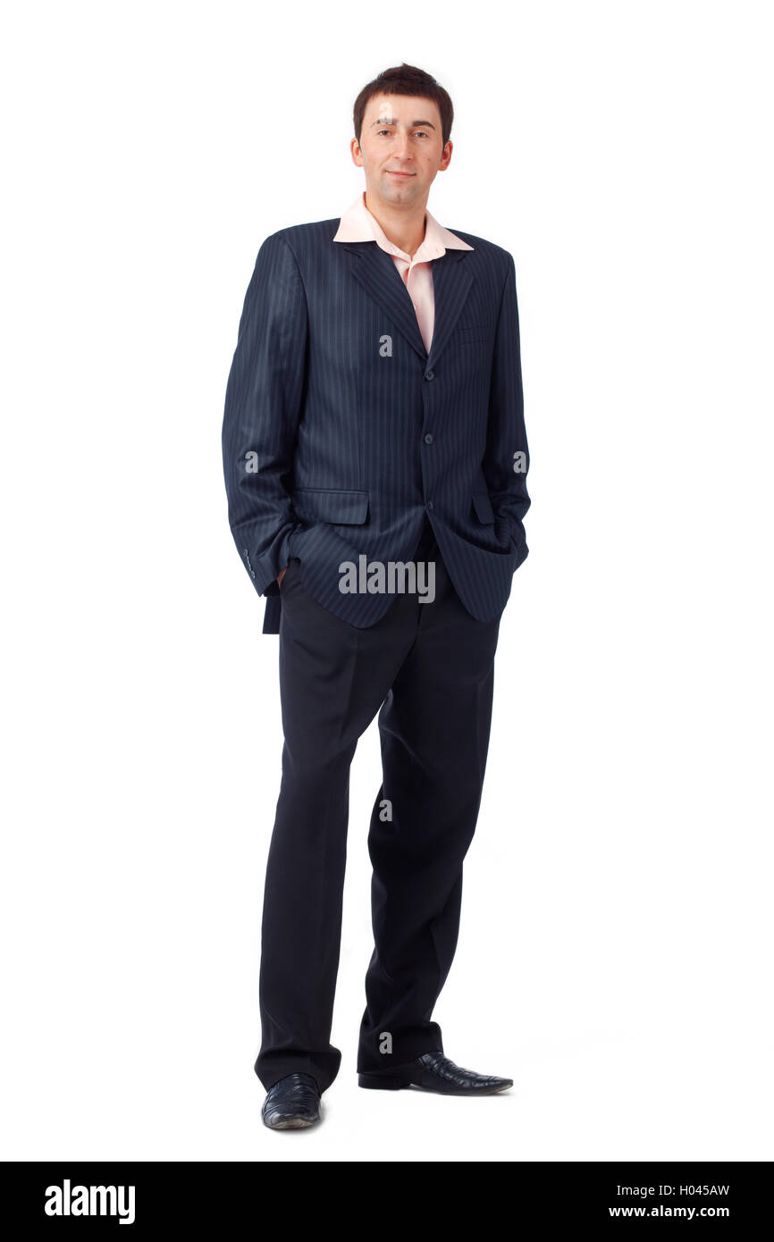 Full length portrait of a young man standing with his hands in pockets. - Stock Image