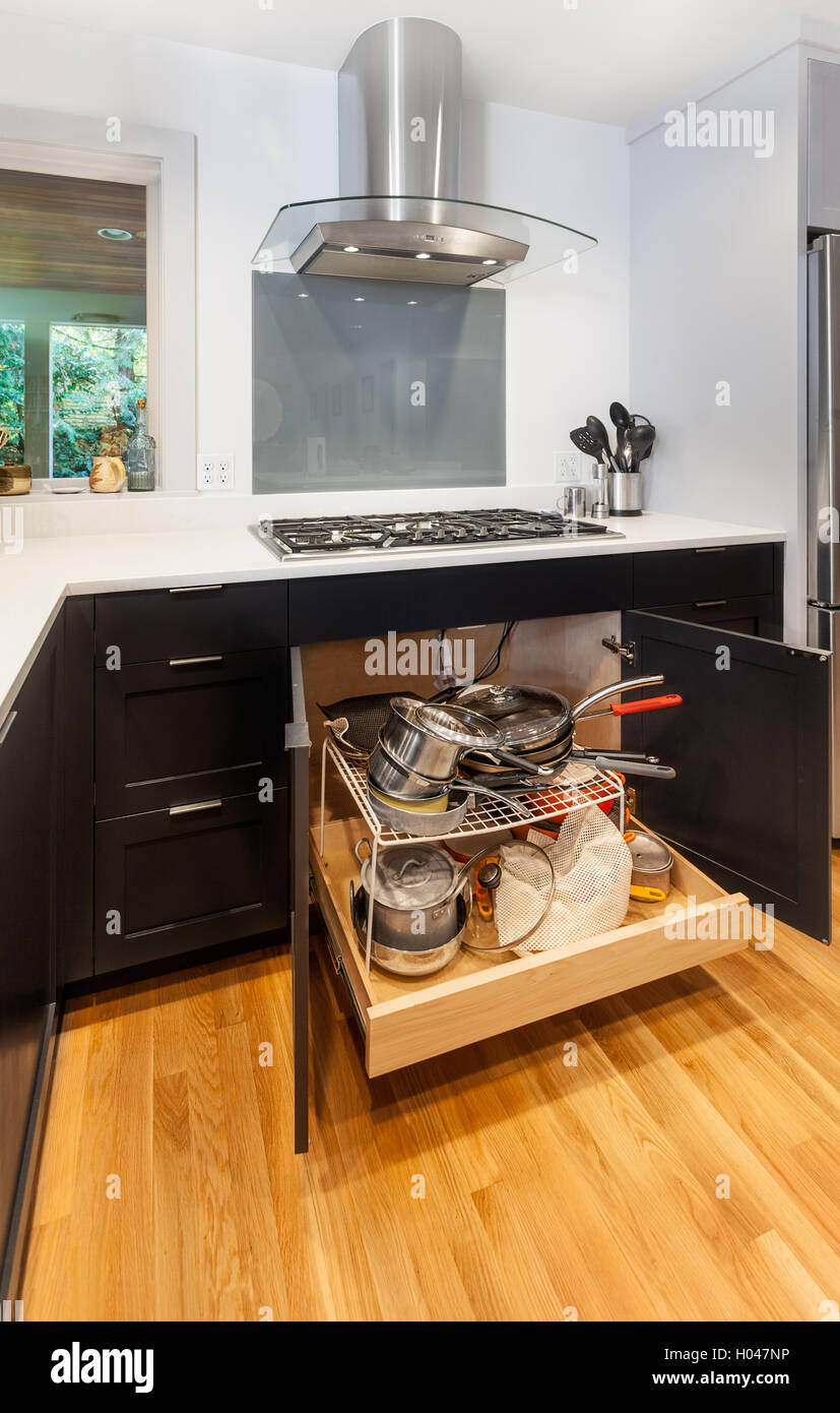 Pullout storage drawer for pots and pans underneath the cooktop - Stock Image