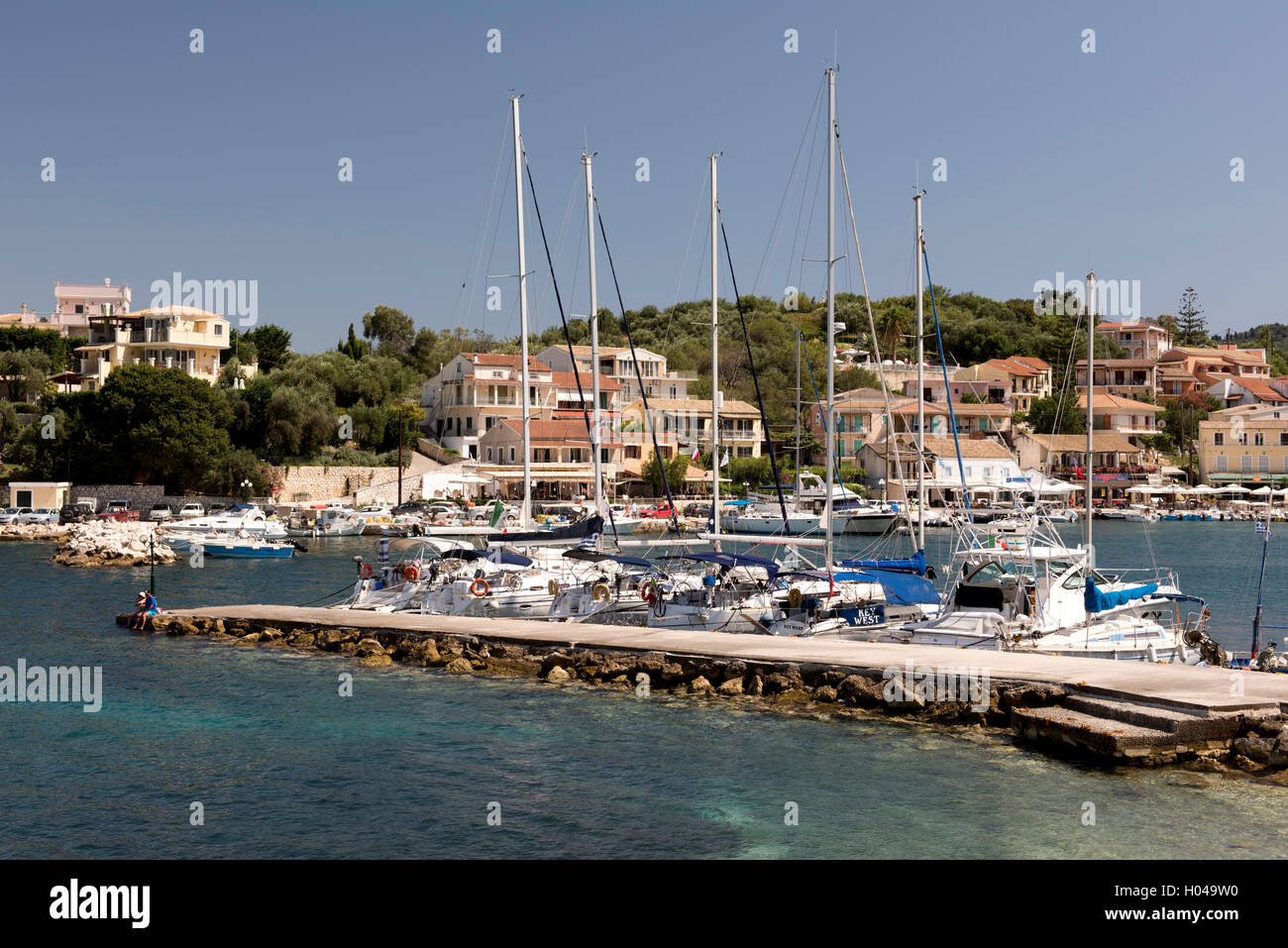 Sailing yachts moored at the entrance to  Kassiopi Harbour in northeast Corfu, The Ionian Islands, The Greek Islands, - Stock Image