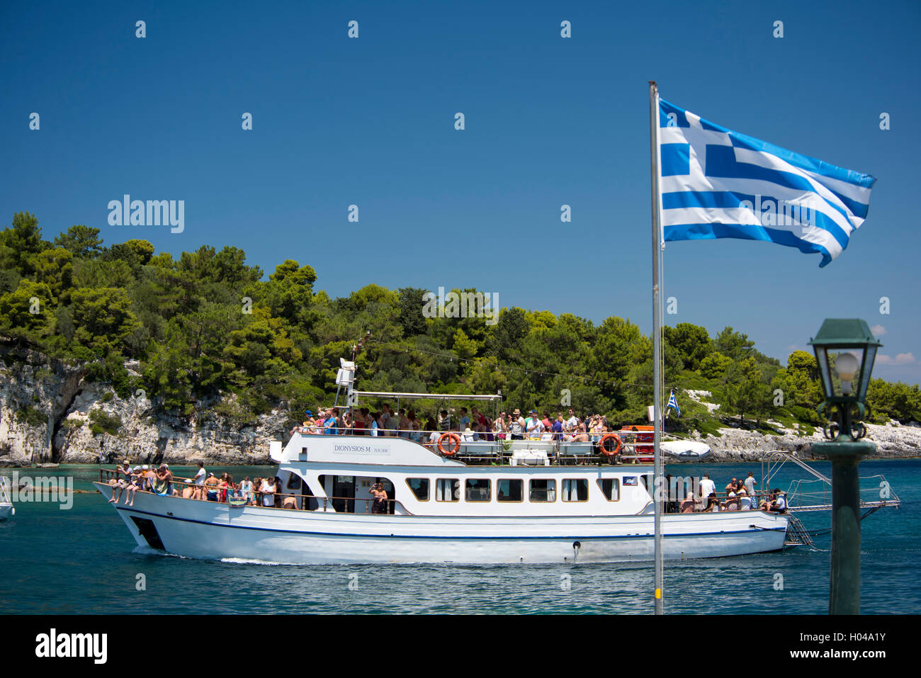 An excursion boat full of tourists heading into Gaios Harbour, Paxos, The Ionian Islands, Greece, Europe - Stock Image