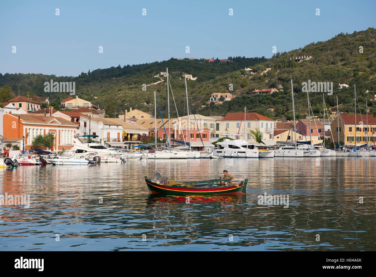A colourful old fishing boat in Gaios harbour at sunrise on Paxos, The Ionian Islands, Greece, Europe - Stock Image