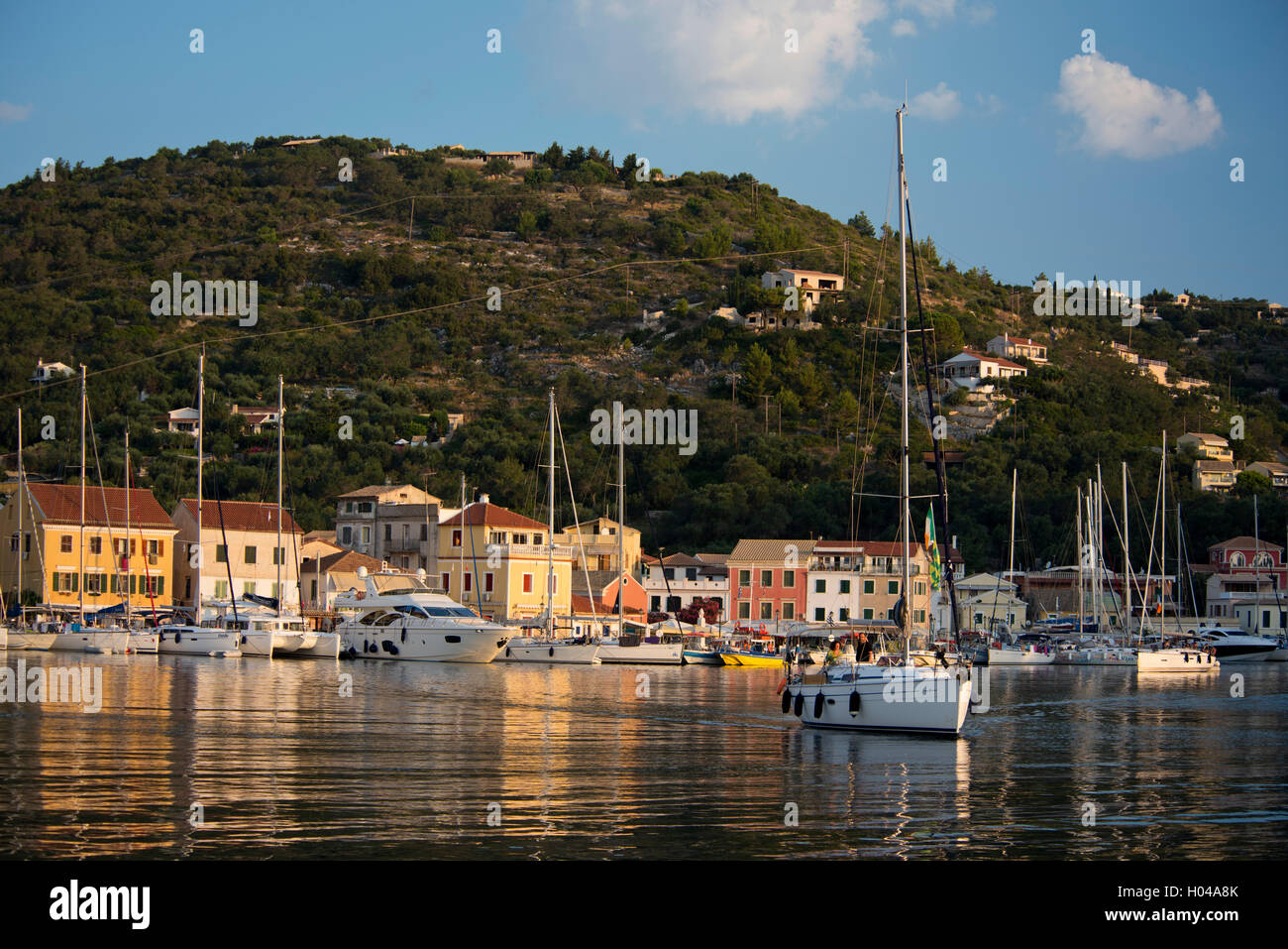 A sailing boat leaving Gaios harbour at sunrise. Paxos, The Ionian Islands, The Greek Islands, Greece, Europe - Stock Image