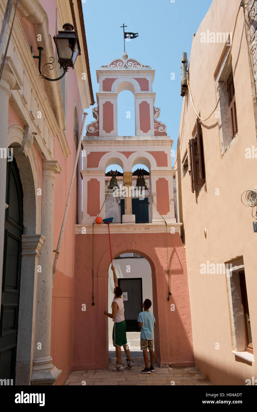 Boys in Gaios retrieving a ball from the bell tower of Agios Triada on the island of Paxos, The Ionian Islands, - Stock Image