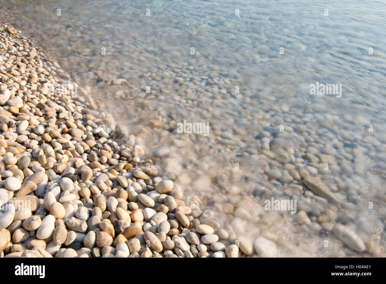 Sea water washing over smoothe rounded stones on Orkos Beach on the island of Paxos, The Ionian Islands, The Greek - Stock Image