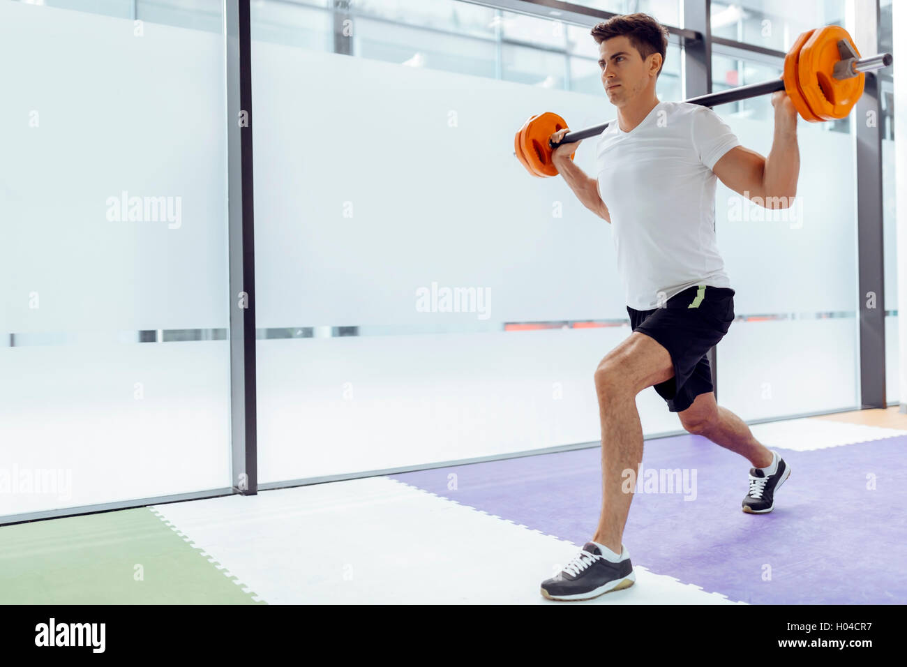 Handsome man exercising and lifting weights in fitness club - Stock Image