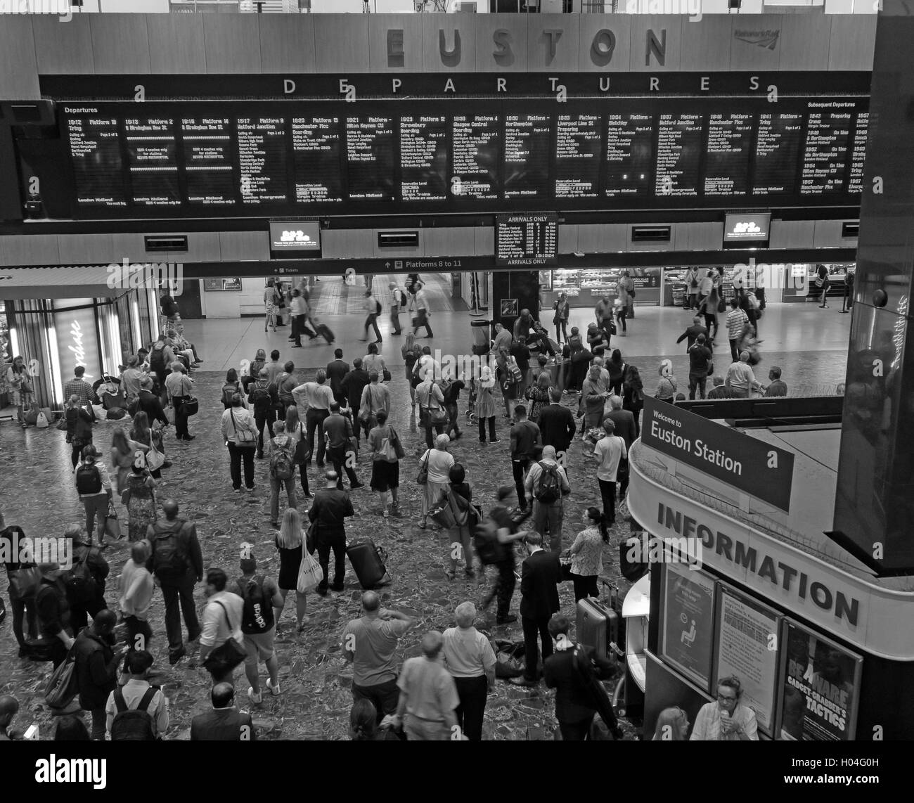 Monochrome Euston railway station departure board and concourse, North London, England, UK - Stock Image