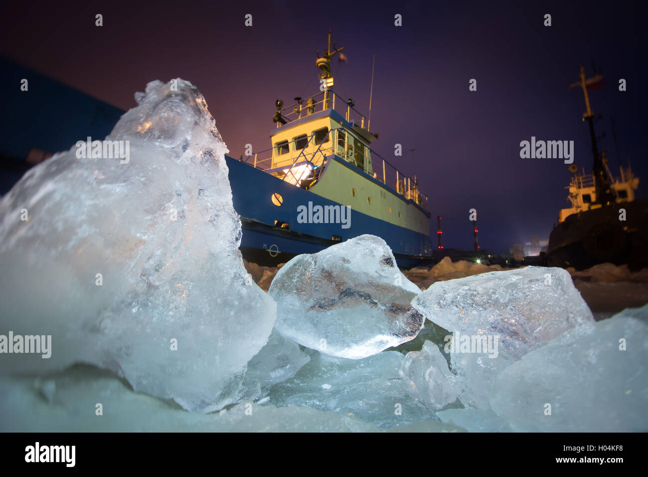 The Icebreaker ship trapped in ice tries to break and leave the bay between the glaciers Stock Photo
