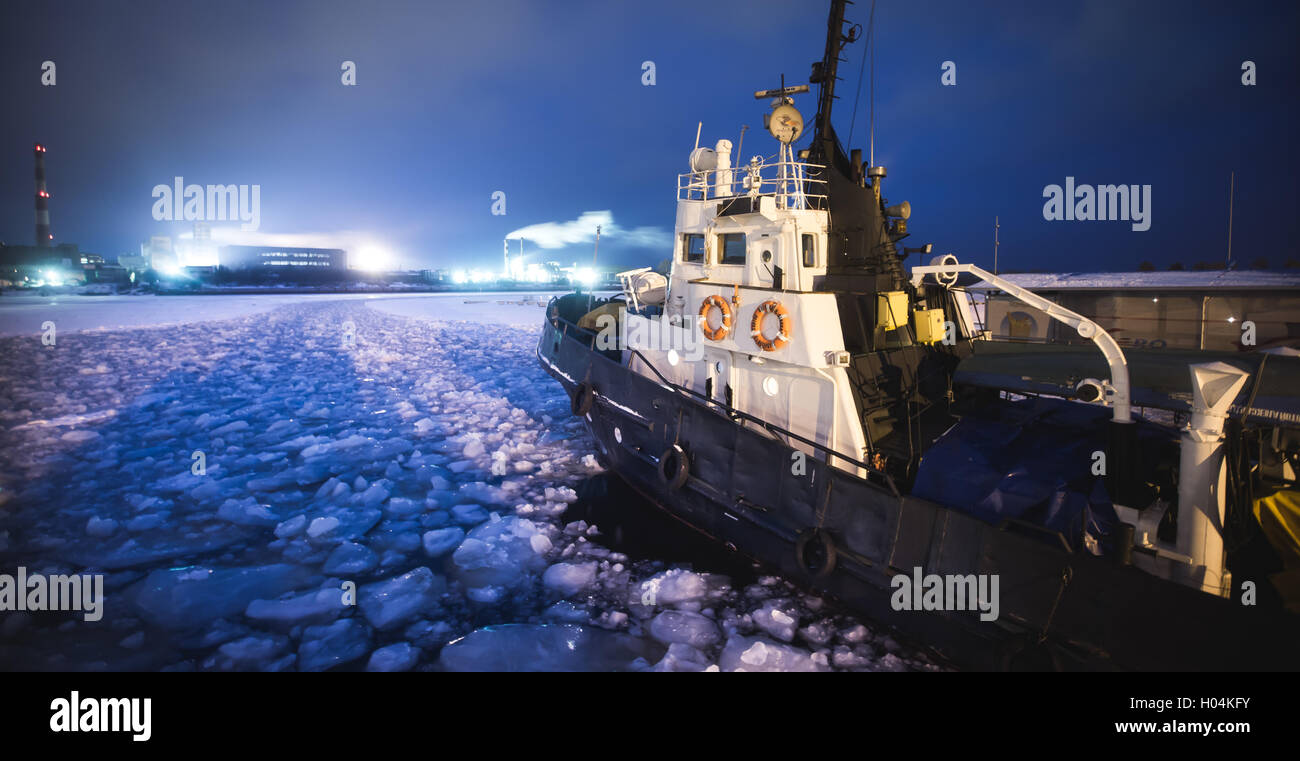 The Icebreaker ship trapped in ice tries to break and leave the bay between the glaciers - Stock Image