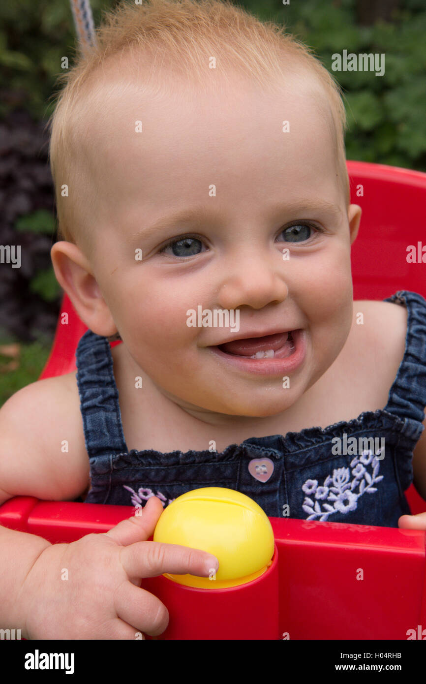 Baby Girl ten months old sitting in garden swing, smiling showing two new bottom teeth. UK. July. - Stock Image