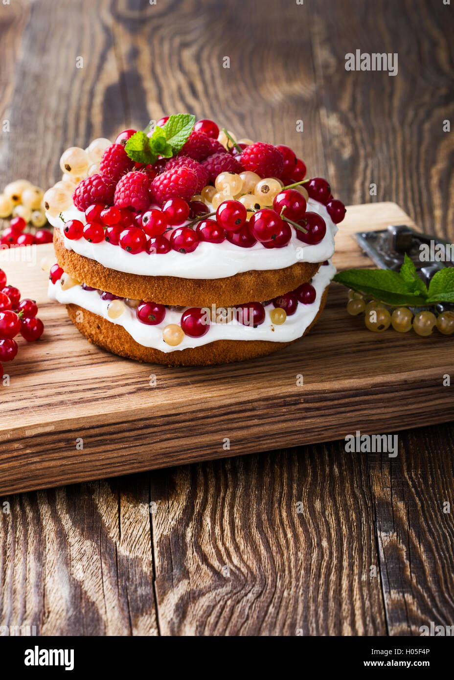 Homemade butter layer cake with whipped cream topping on rustic wooden table - Stock Image