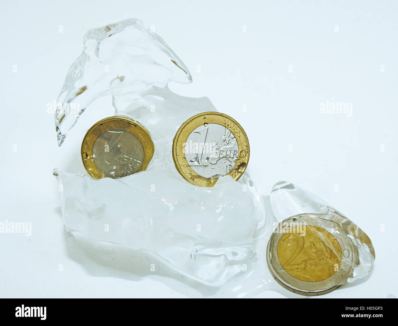 Cache euro coins in ice. - Stock Image