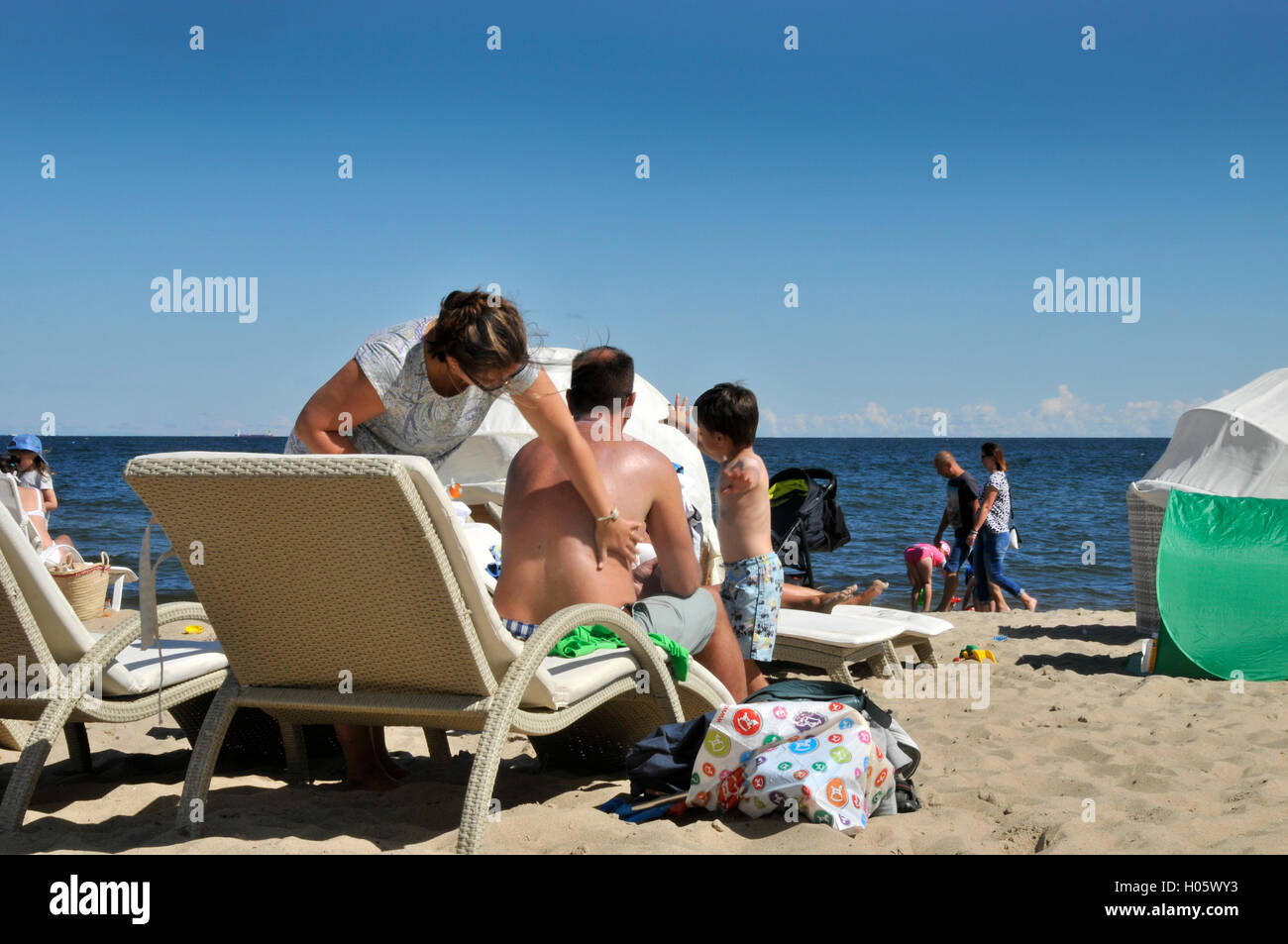 woman applying sun tan lotion to husbands back - Stock Image