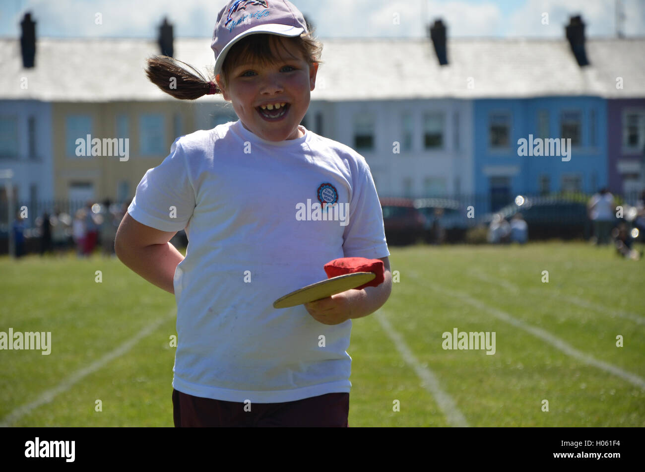 Portrush , Northern Ireland - June 12th, 2013 :- Sports Day A young female child runs down a track balancing a bean - Stock Image