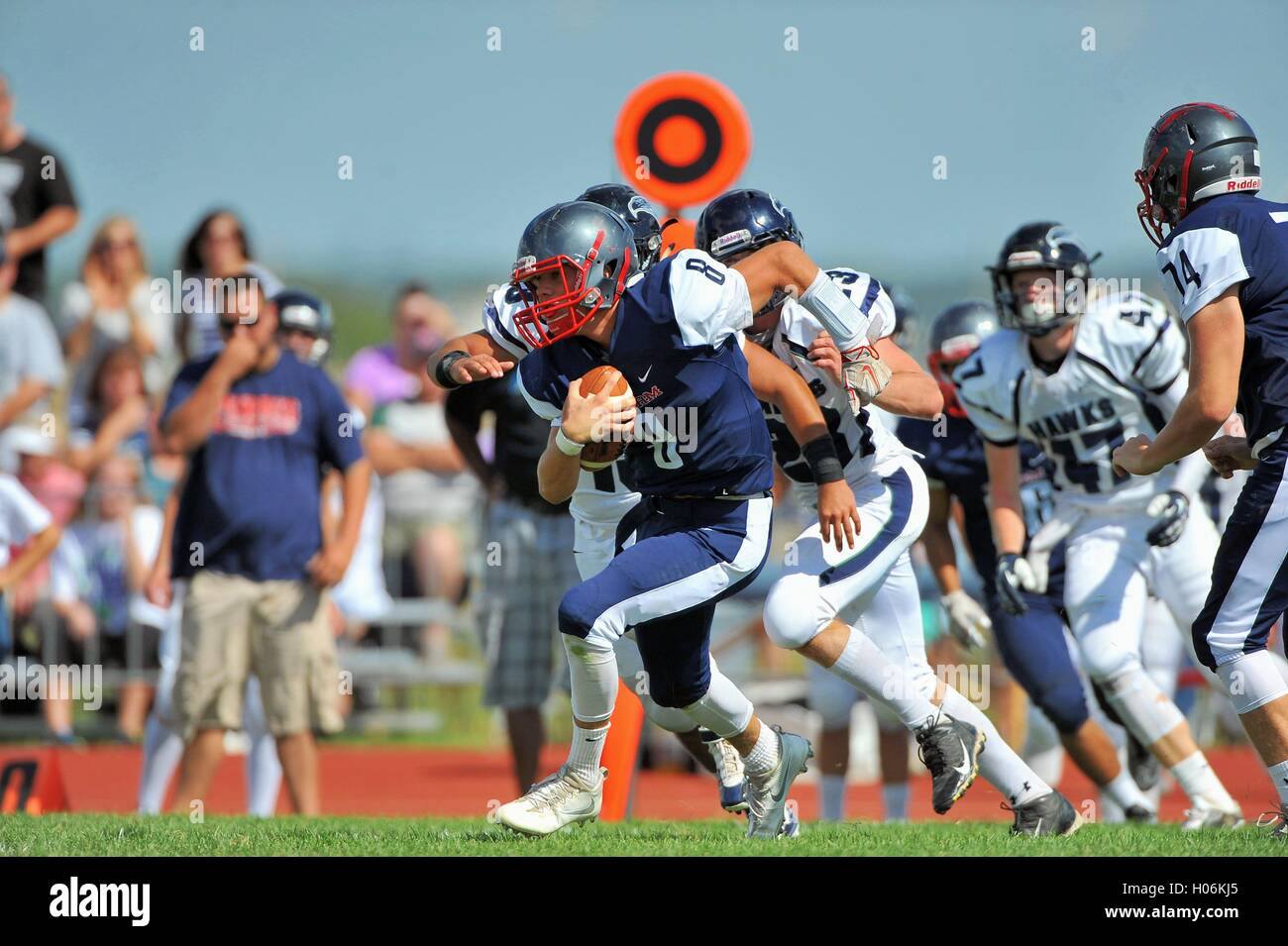 A high school quarterback on the loose scrambling for yardage against into the open and a first down. USA. - Stock Image