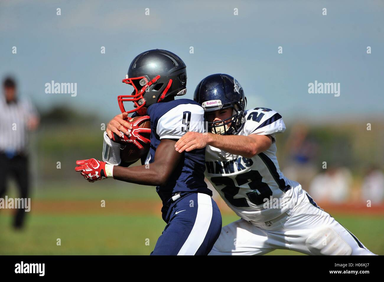 Defensive back wrapping up an opposing running back in making a solo tackle during a high school football game. - Stock Image