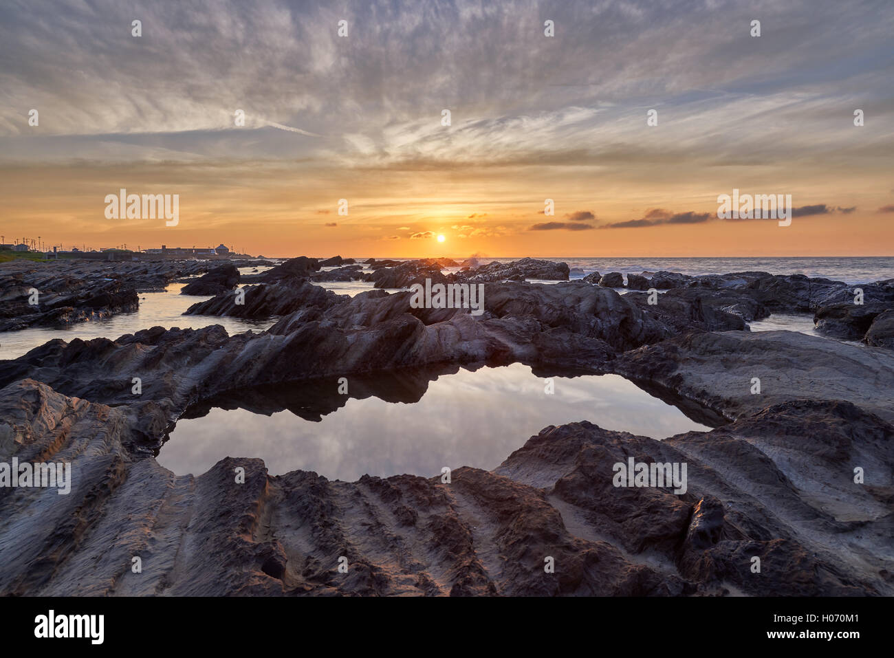 Sunrise light hitting sea rocks by the beach in the morning in Minamiboso, Chiba Prefecture, Japan - Stock Image