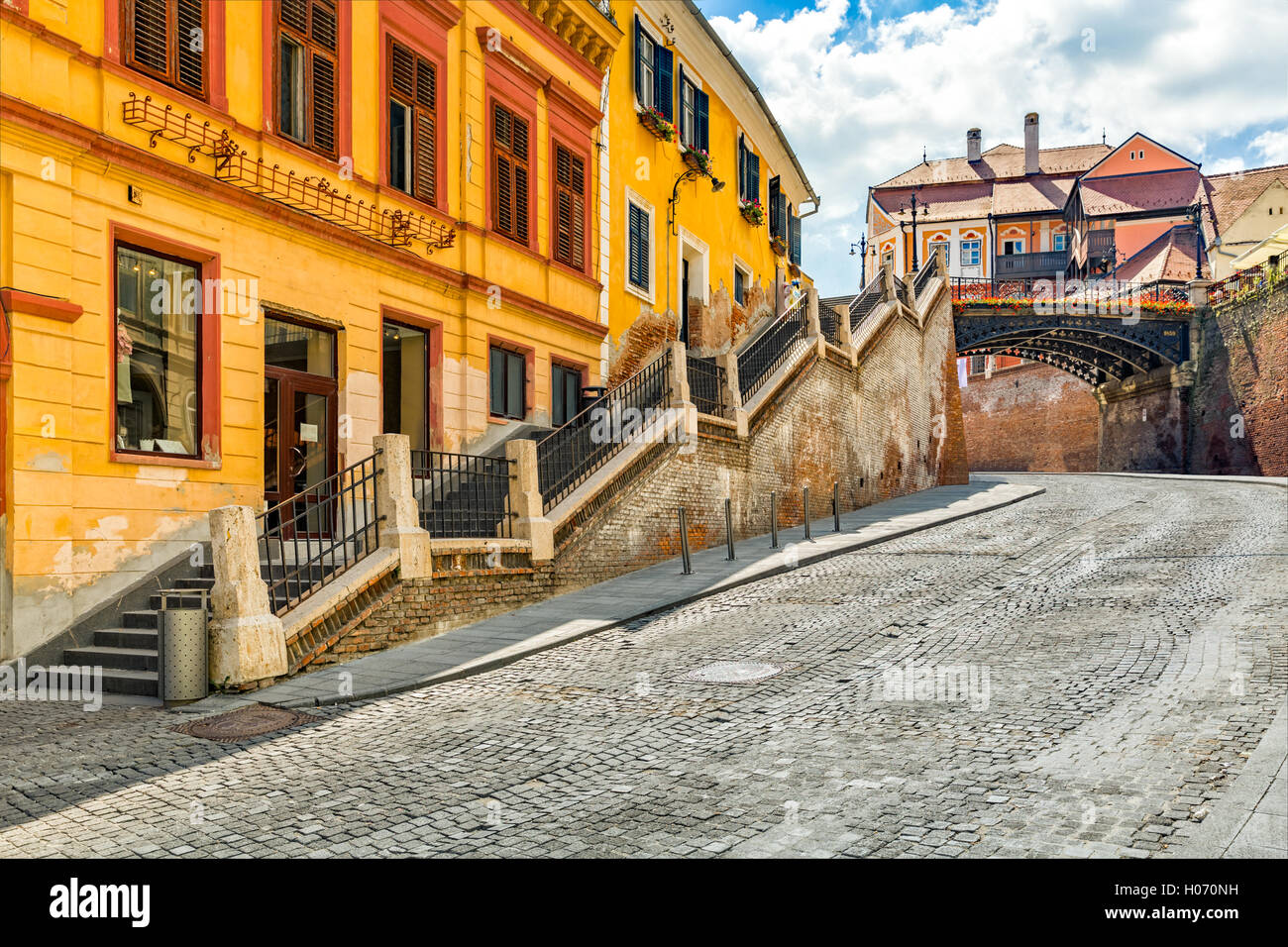 Cobblestone street passes under The Bridge of Lies, a landmark of the old town of Sibiu, Romania - Stock Image