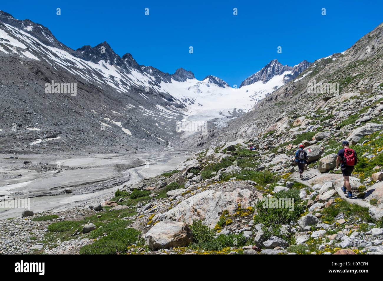 Two male hikers approach Oberaargletscher, a glacier in the Swiss Alps in the Grimsel region of Berner Oberland, - Stock Image