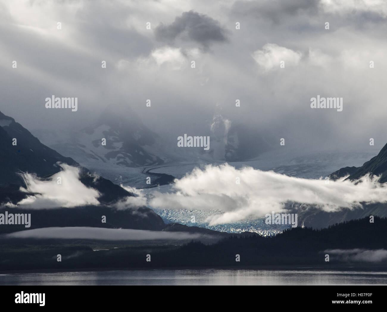 Dawn sun shines on fog and clouds, illuminating Grewingk Glacier. - Stock Image