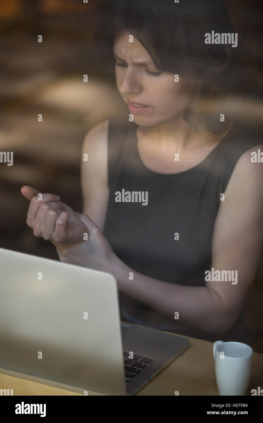 Young woman sitting in front of laptop, touching her aching wrist, frowning with pained expression, got repetitive - Stock Image