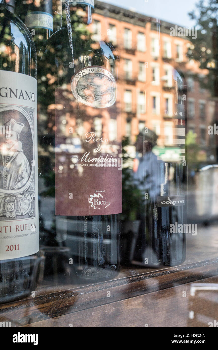 choice bottles red wine glimmer in vitrine of Italian restaurant as glass reflects zoning protected 19th century - Stock Image