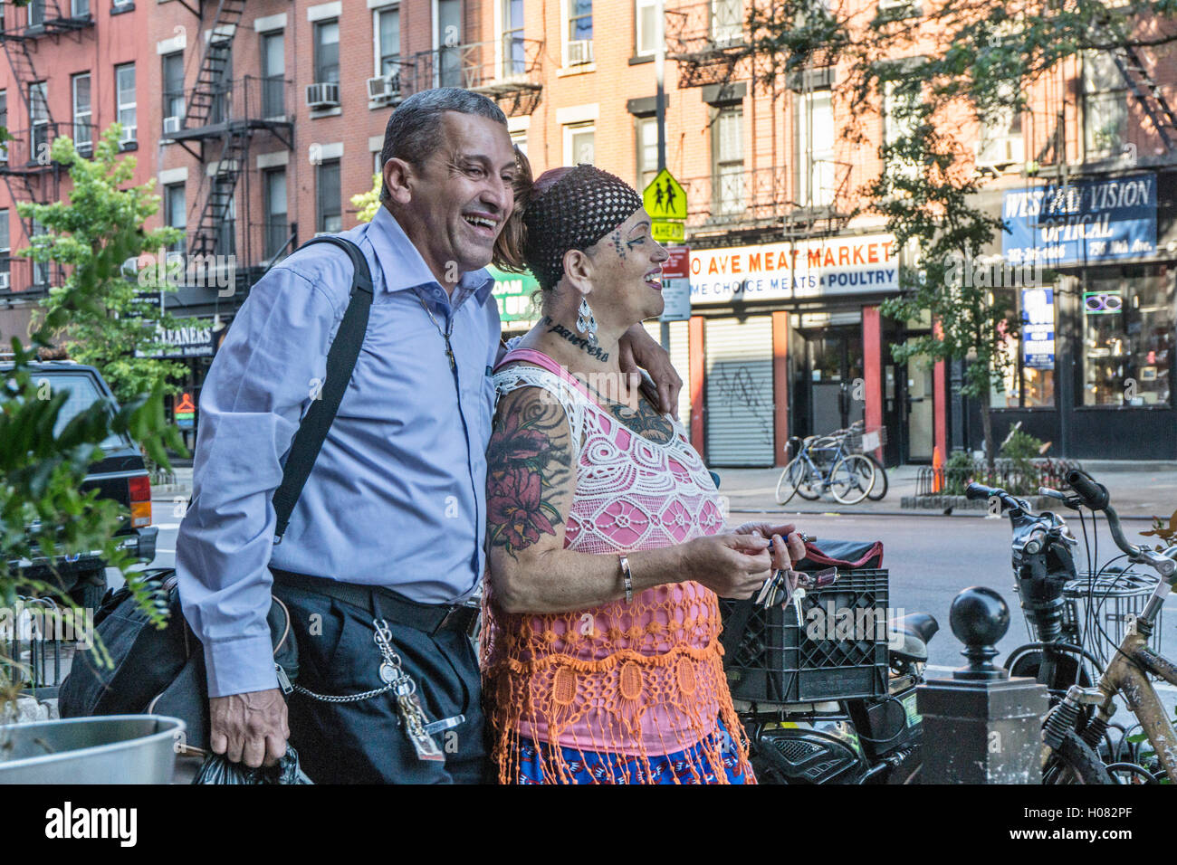happy older couple promenade on 10th Avenue she garlanded with fantastic tattoos & colorful garb he with arm - Stock Image