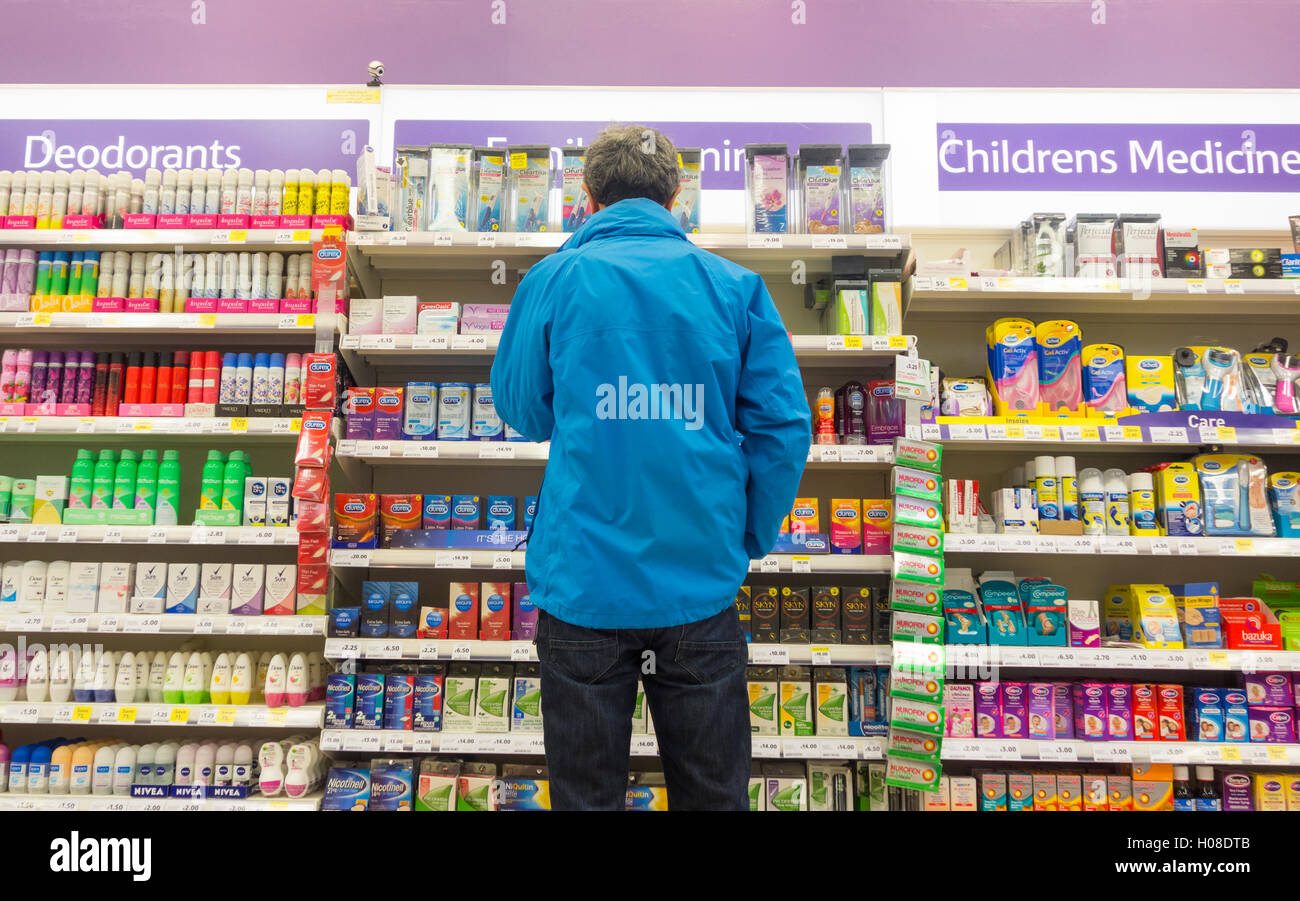 Man looking at Family planning (condoms) display in supermarket. UK - Stock Image