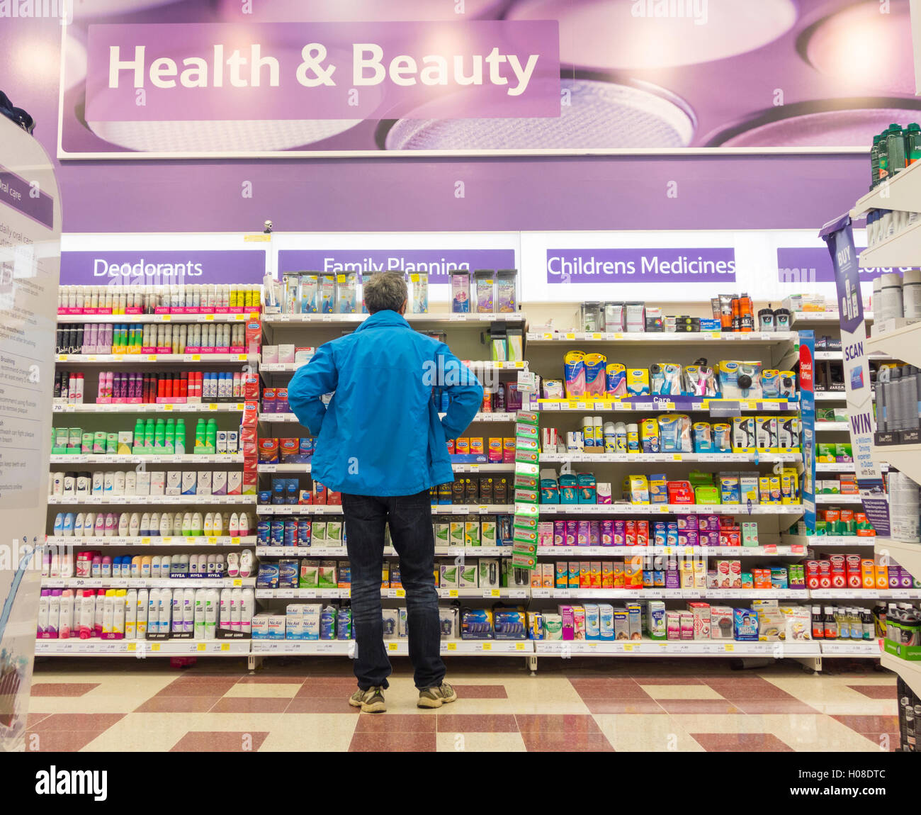 Man looking at Family planning (condoms) display in Tesco supermarket. UK - Stock Image