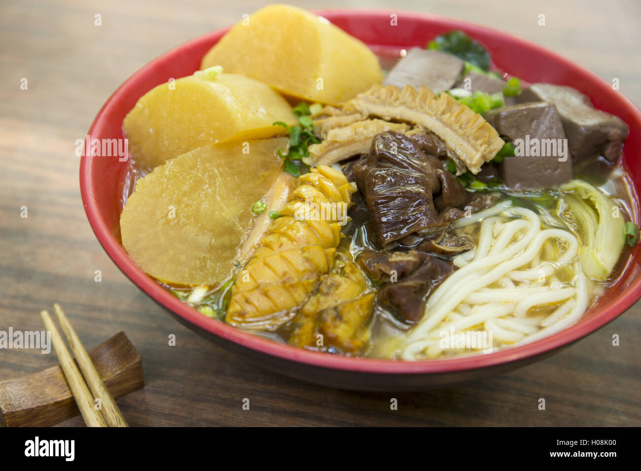 Chinese bowl of noodle with squid, dried pig blood and radish on the table - Stock Image