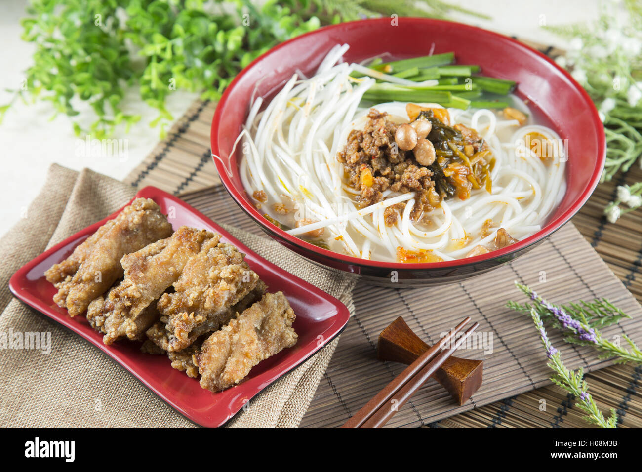 Chinese bowl of noodle with fried pork ribs and herbs on the table - Stock Image