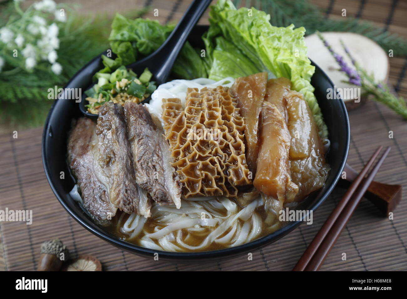 Chinese bowl of vermicelli noodle with fried beef, cow's stomach and salad on the table - Stock Image
