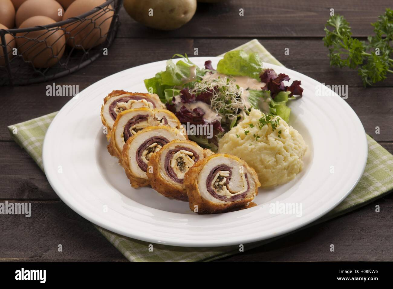 Plate of Ayam with potato and herbs on the table in restaurant - Stock Image
