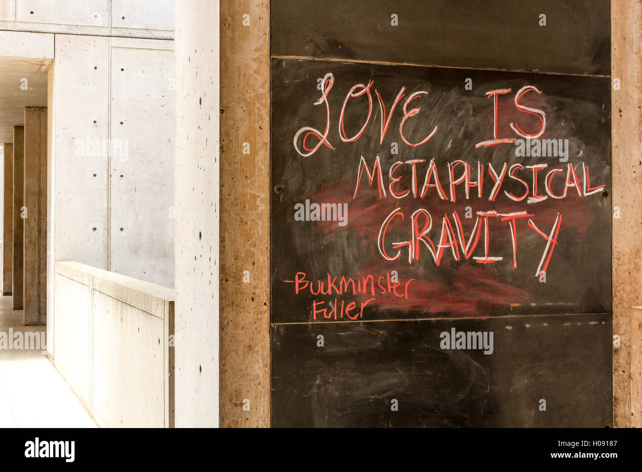 Quote: 'love is metaphysical gravity' by Buckminster Fuller on blackboard wall of a building. - Stock Image