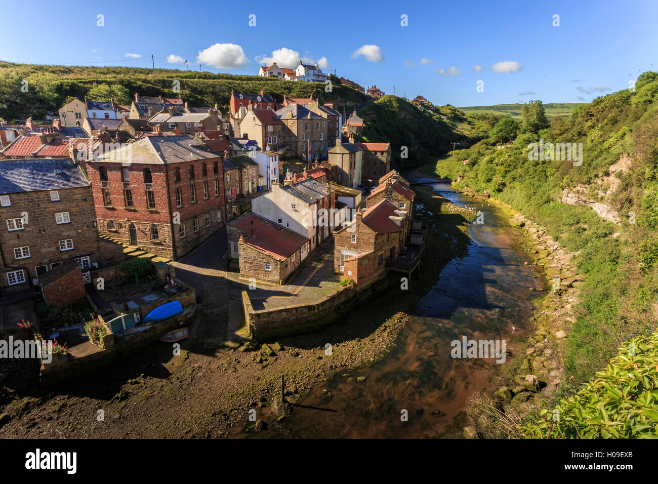 Steep streets of fishing village nd river, elevated view in summer, Staithes, North Yorkshire Moors National Park, - Stock Image