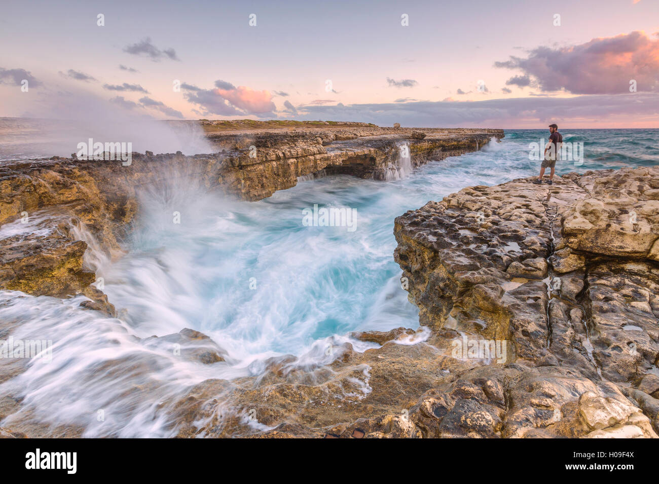 Hiker on the cliffs admires the crashing waves at Devil's Bridge, Antigua, Antigua and Barbuda, Leeward Islands, - Stock Image