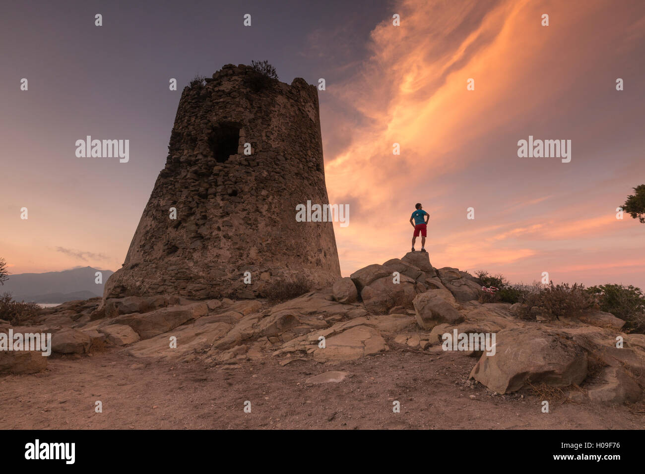 Hiker admires sunset from the stone tower overlooking the bay, Porto Giunco, Villasimius, Cagliari, Sardinia, Italy - Stock Image