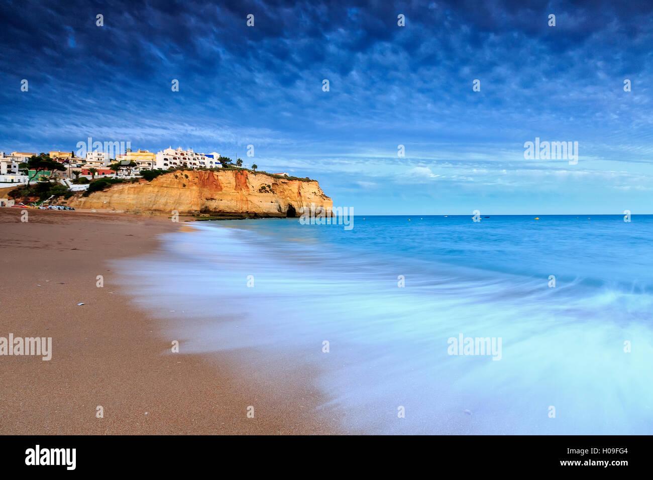 Ocean waves crashing on rocks and beach surrounding Carvoeiro village at sunset, Lagoa Municipality, Algarve, Portugal, Stock Photo