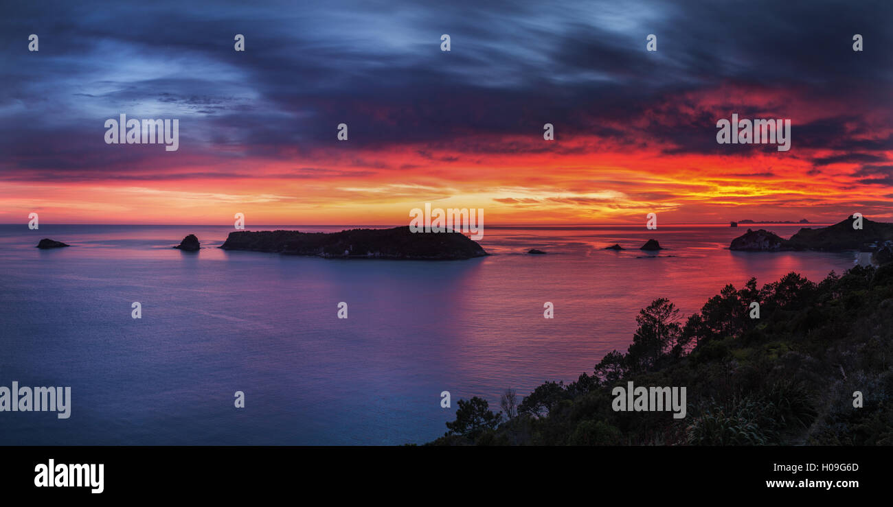 A fiery dawn sky breaks beyond the islands off the Coromandel Peninsula, Waikato, North Island, New Zealand, Pacific - Stock Image