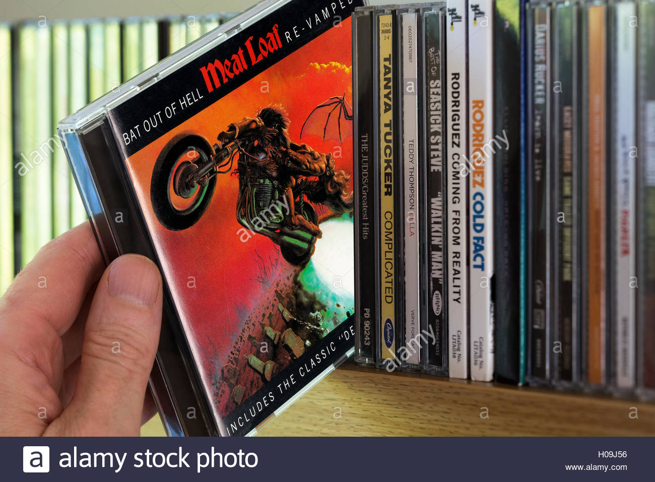 Meat Loaf Album Bat Out Of Hell CD being chosen from a shelf of other CD's - Stock Image