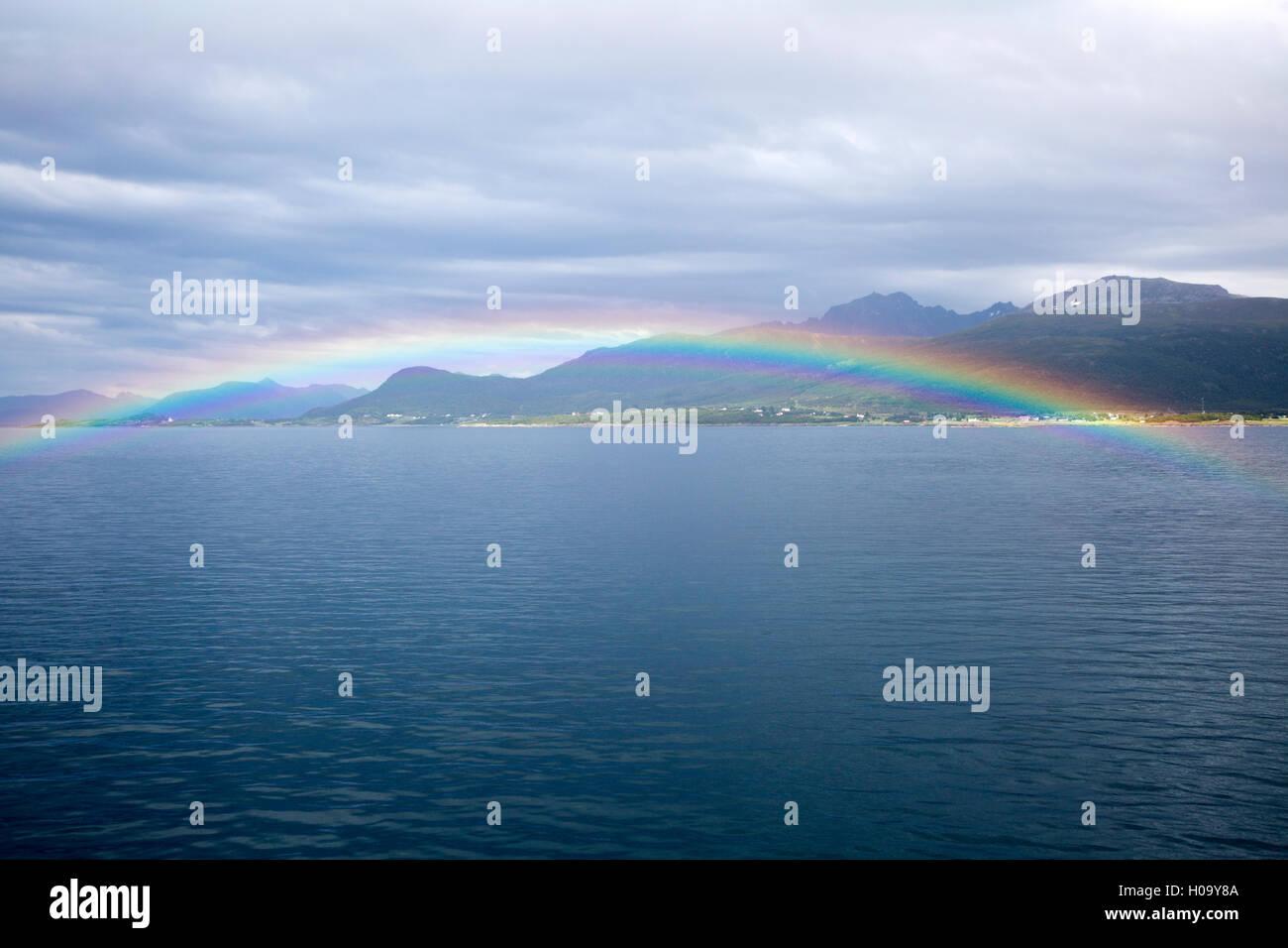 Rainbow over sea near Stokmarknes, Hadsel municipality, Hadseloya island, Nordland, Vesteralen region, northern - Stock Image