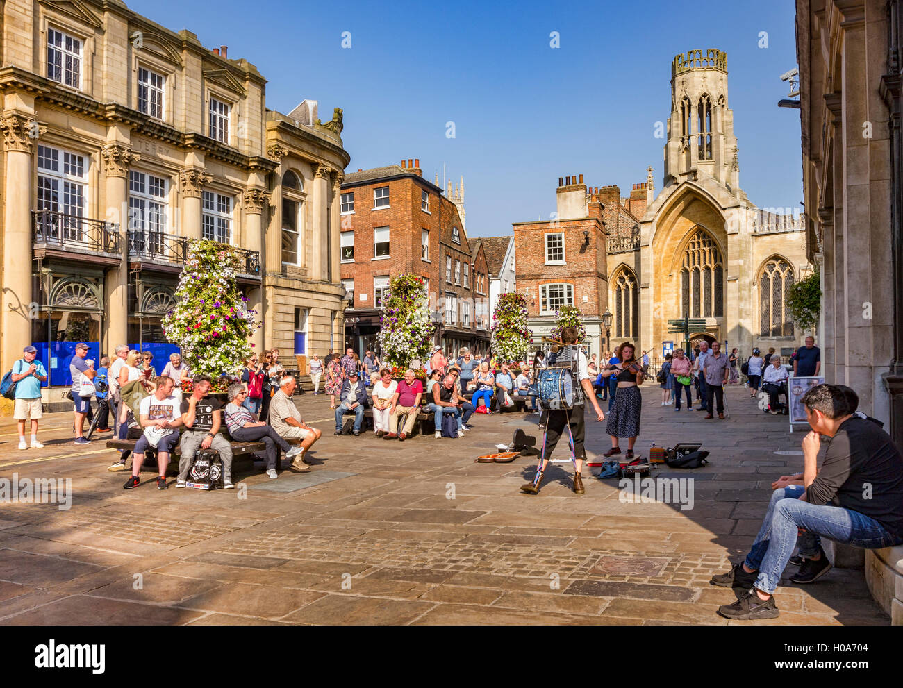 Crowds watching one man band busking in St Helen's Square, York, North Yorkshire, England, UK - Stock Image